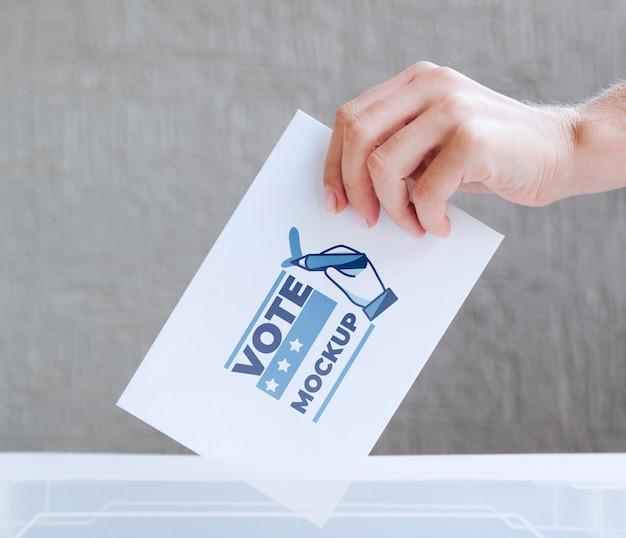 Mano del primo piano che mette modello di scheda elettorale nella casella