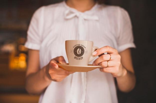 Mani del primo piano che tengono tazza di caffè