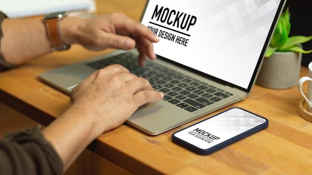 Chiuda in su delle mani maschile digitando sul mockup del computer portatile