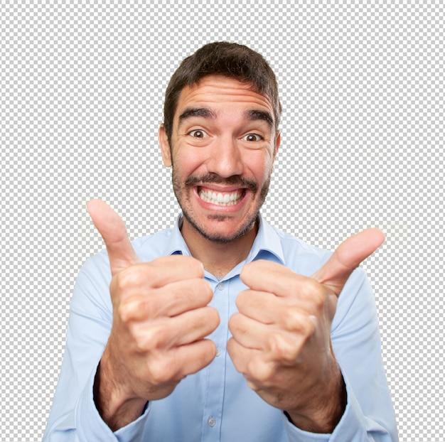Primo piano di un giovane uomo soddisfatto con i pollici in su