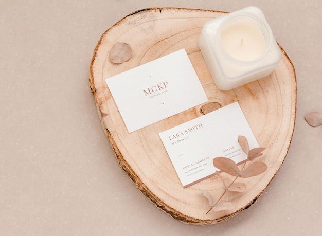 Primo piano di due modelli di biglietti da visita minimalisti con foglie e candela su un baule