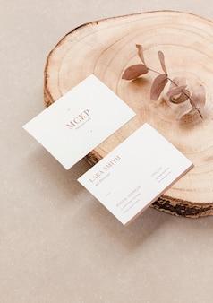 Primo piano di due modelli di biglietti da visita ed elementi organici per la presentazione del marchio