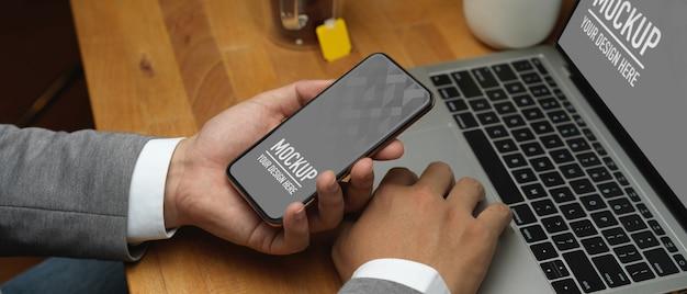 Vista ravvicinata della mano di uomo d'affari che tiene smartphone mockup