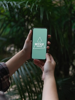 Vista ravvicinata delle mani femminili che tengono mock up smartphone mentre vi rilassate in giardino