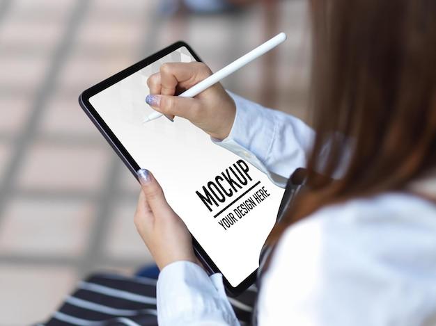 Vista ravvicinata della donna utilizzando il mockup di tavoletta digitale