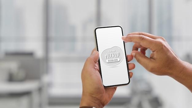 Vista ravvicinata delle mani utilizzando mock up smartphone su sfondo sfocato dell'interno