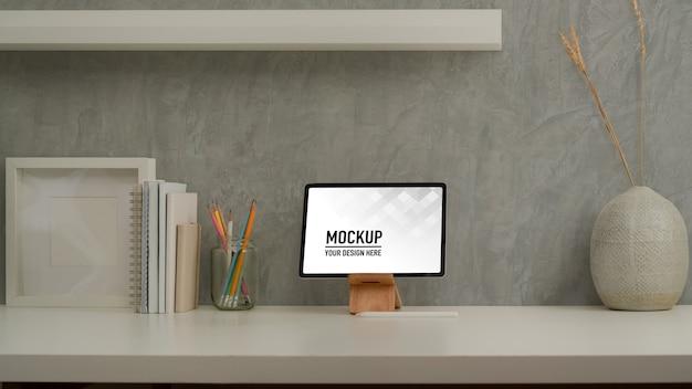 Vista ravvicinata della scrivania da casa con mock up tablet, cancelleria, decorazioni e copia spazio