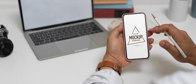Vista ravvicinata di imprenditore maschio utilizzando mock up smartphone mentre si lavora con il computer portatile sul tavolo da lavoro