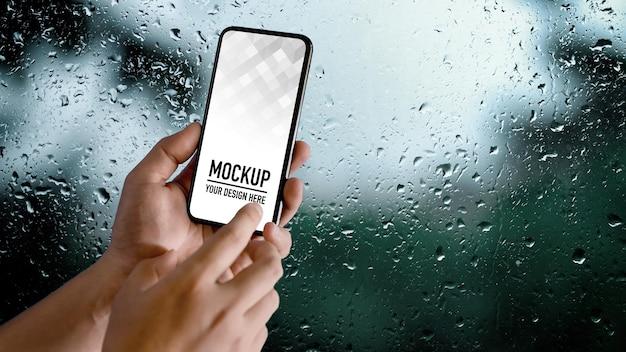 Vista ravvicinata delle mani maschile utilizzando lo smartphone mockup