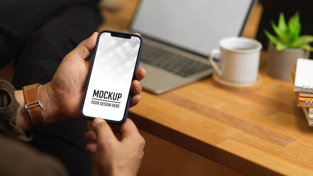 Vista ravvicinata delle mani maschile utilizzando il mockup dello smartphone