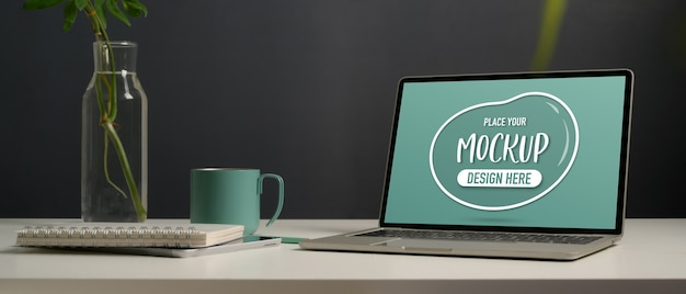 Vista ravvicinata di mock up laptop, cancelleria, vaso di piante e tazza sulla scrivania bianca in ufficio a casa
