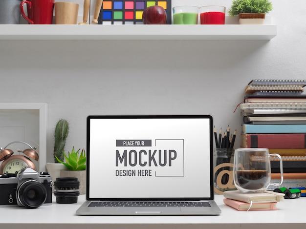 Vista ravvicinata del mock up laptop sul tavolo di studio con elementi di scuola e decorazioni
