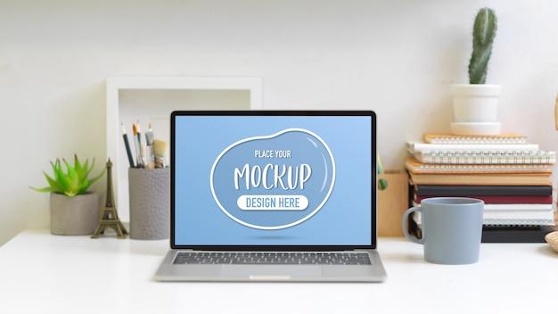 Vista ravvicinata della scrivania da ufficio con mock up laptop, libri, cancelleria e decorazioni