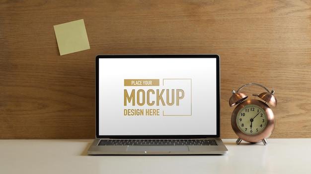 Vista ravvicinata dell'area di lavoro con laptop mockup, orologio e nota adesiva sulla parete in legno