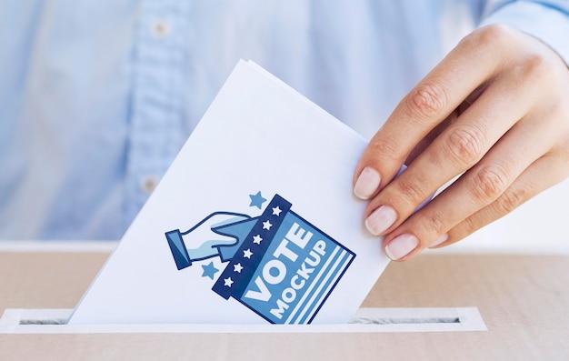 Donna del primo piano che mette modello di scheda elettorale nella casella