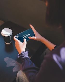 Chiuda in su della donna che utilizza smartphone nella caffetteria