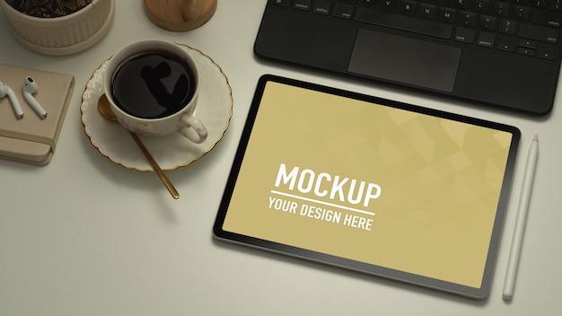 Primo piano dell'area di lavoro con tablet, tastiera, tazza di caffè e mockup di forniture