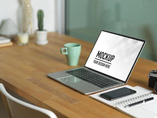 Primo piano sul tavolo da lavoro con mockup di laptop