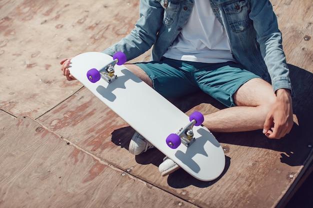 Chiuda in su giovane che tiene il mockup di skateboard