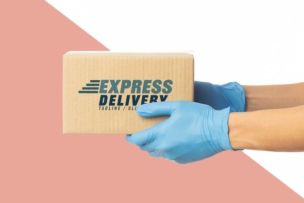 Mano del fattorino del primo piano in guanti medici che tengono il modello del modello della scatola di cartone.