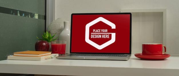 Vista del primo piano del mock up laptop in un ambiente di lavoro moderno con una tazza di caffè rosso e decorazioni