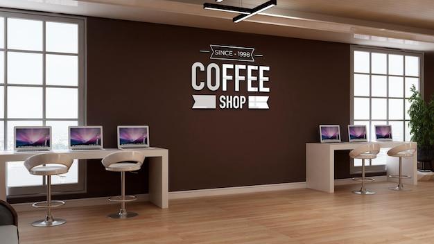 Mockup del logo della caffetteria nella segnaletica della parete del caffè con scrivania per laptop con tema dell'area di lavoro