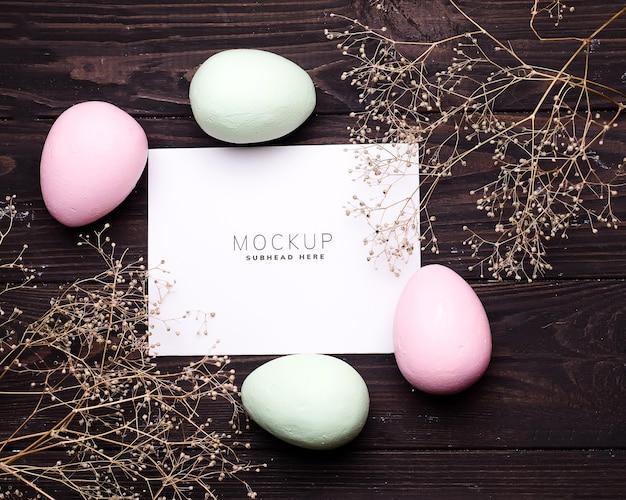 Uova di pasqua colorate e fiori sul modello di carta