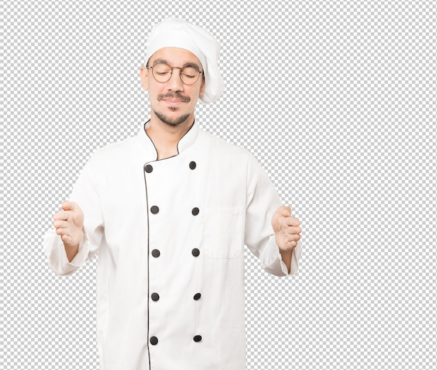 Giovane cuoco unico sicuro che fa un gesto di tenere qualcosa con le sue mani