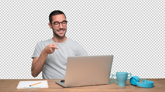 Fiducioso giovane uomo seduto alla sua scrivania e indicando con la mano