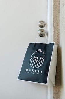 Modello di borsa da forno per la consegna senza contatto appeso a una maniglia durante la pandemia di coronavirus