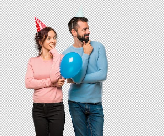 Coppia con palloncini e cappelli di compleanno guardando al lato con la mano sul mento