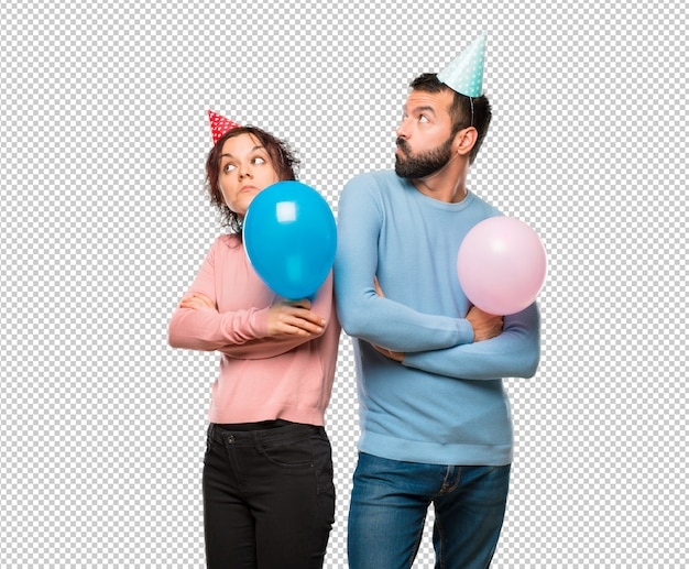 Coppia con palloncini e cappelli di compleanno facendo un gesto poco importante mentre si solleva le spalle