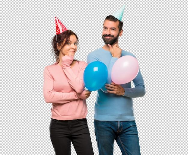 Coppia con palloncini e cappelli di compleanno sorridenti e guardando in avanti con la faccia fiduciosa