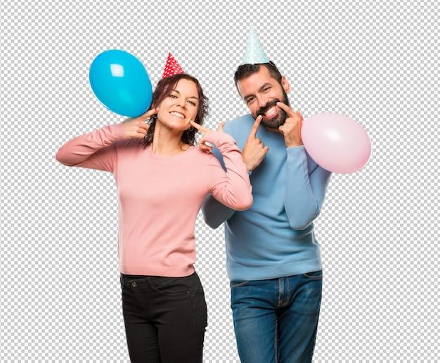 Coppia con palloncini e cappelli di compleanno sorridenti con una piacevole espressione
