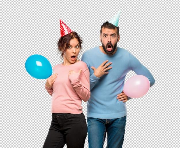 Coppia con palloncini e cappelli di compleanno sorpreso e scioccato. emozioni facciali espressive