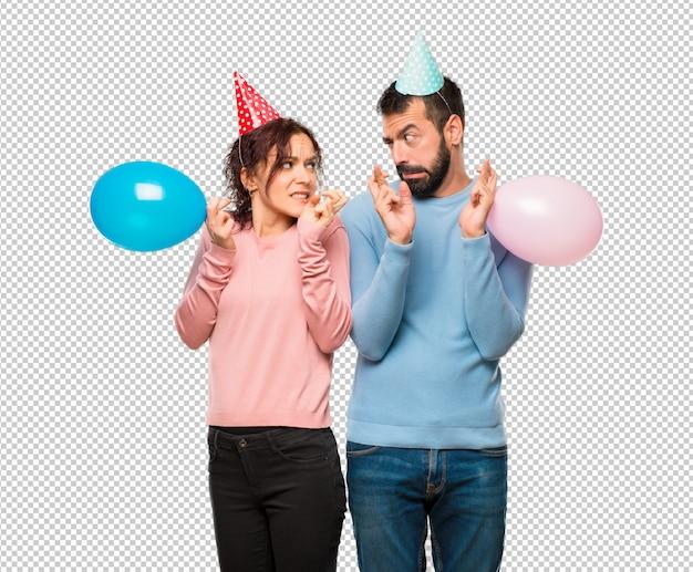 Coppia con palloncini e cappelli di compleanno con le dita che attraversano e che desiderano il meglio