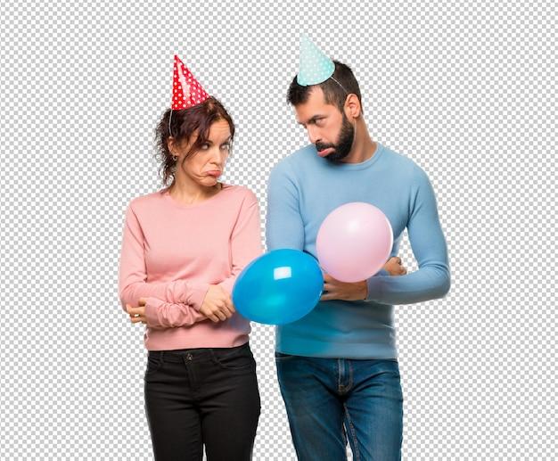Coppia con palloncini e cappelli di compleanno con espressione triste e depresso. gesto serio