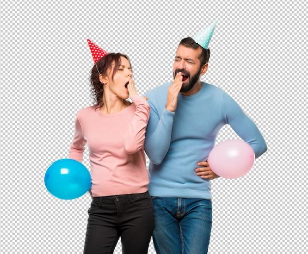 Coppia con palloncini e cappelli di compleanno sbadigliando e coprendo la bocca con la mano. espressione assonnata