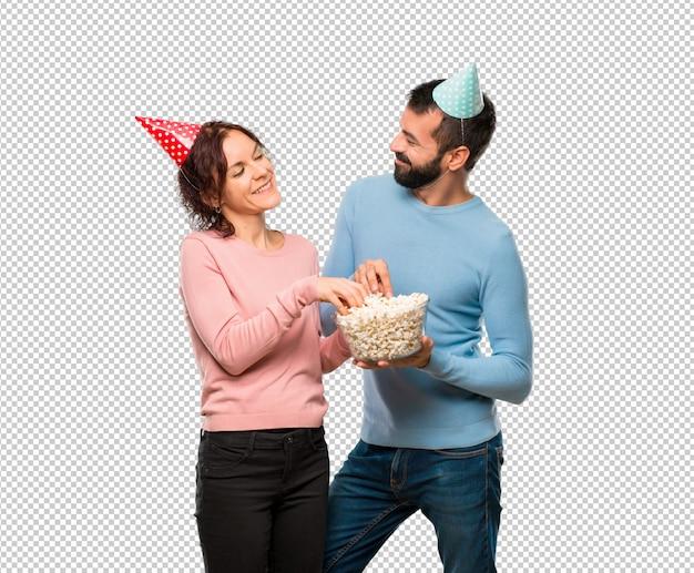 Coppia con cappelli di compleanno e mangiando popcorn