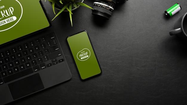 Spazio di lavoro scuro e piatto creativo con fotocamera tablet digitale per smartphone