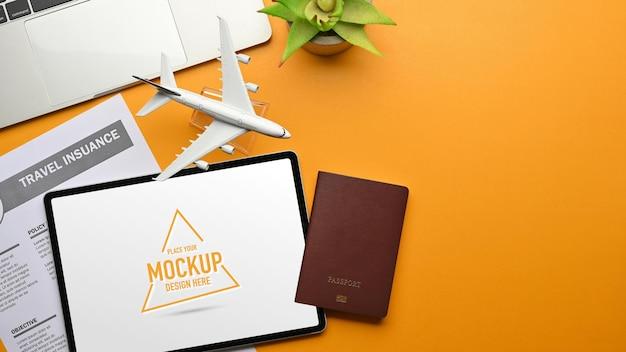 Area di lavoro piatta creativa nel concetto di viaggio con laptop assicurazione di viaggio passaporto tavoletta digitale