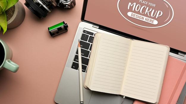 Area di lavoro piatta creativa con laptop notebook aperto e fotocamera sul tavolo rosa