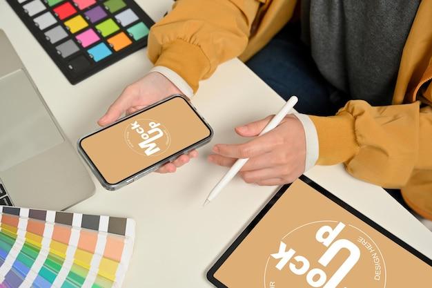 Ritagliata colpo di mani femminili designer che lavorano con lo smartphone