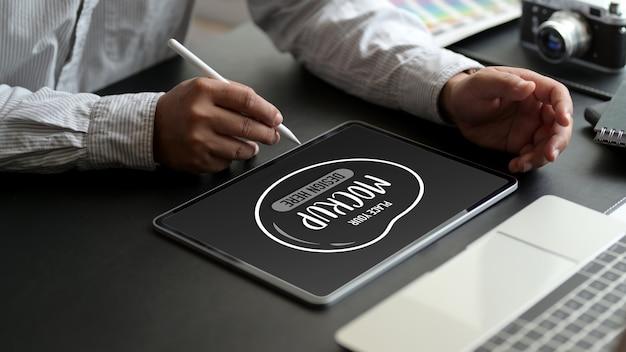Ritagliata colpo di lavoratore di sesso maschile che scrive ing su mock up tavoletta digitale con penna stilo sulla scrivania in ufficio