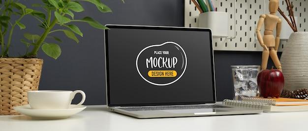 Ritagliata colpo di mock up laptop sul tavolo di lavoro