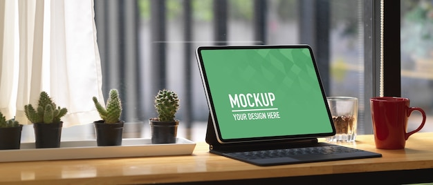 Ritagliata colpo di area di lavoro portatile con mock up tablet sulla barra di legno nella caffetteria