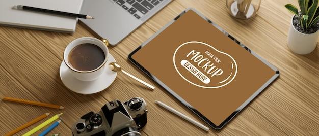 Colpo ritagliato del tavolo da studio con tablet mock up con cancelleria su tavola di legno illustrazione 3d