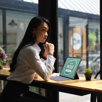 Ritagliata colpo di pensieroso impiegato femminile seduto con mock up tavoletta digitale