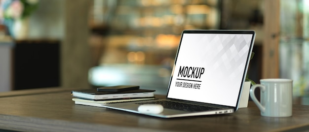 Colpo ritagliato del tavolo da lavoro con mockup di laptop