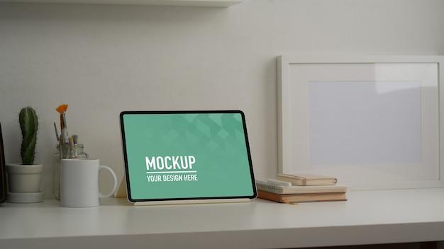 Ritagliata colpo di tavolo da lavoro con mock up tablet, cancelleria e decorazioni nella stanza dell'home office